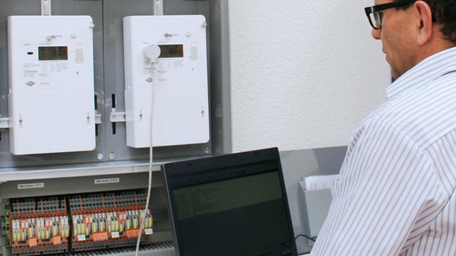 Mann arbeitet mit Laptop vor modernen Stromzählern.