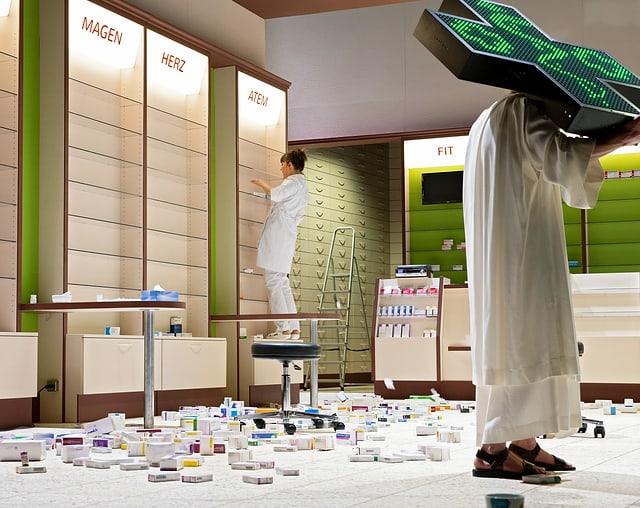 Ein Mann trägt ein Apothekerkreuz, dahinter räumt eine Frau die Regale eienr Apotheke aus.