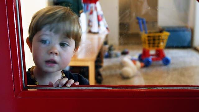 Ein Kind schaut durch die Glasscheibe einer Tür in einer Berner Kindertagesstätte