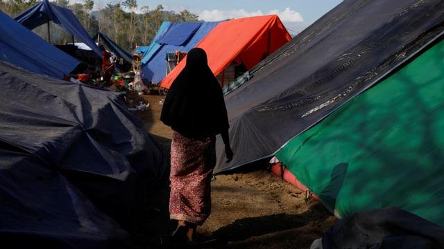 Frau von hinten in einem improvisierten Zeltlager auf Lombok.