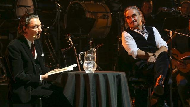 Martin Suter und Stephan Eicher sitzen gemeinsam auf einer Bühne.