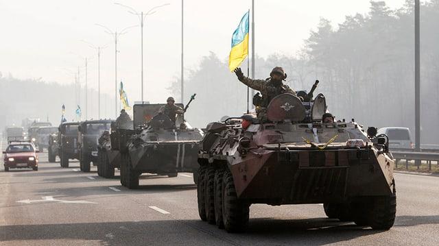 Symbolbild: Ukrainische Militärfahrzeuge mit blau-gelber Flagge defilieren auf einer Strasse.