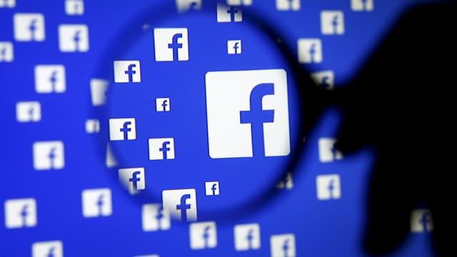 Eine Person hält eine Lupe vor einen Bildschirm mit Facebook-Logos.