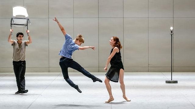 Drei Künstler tanzen auf einer hellen Bühne.