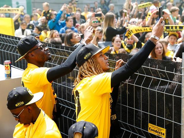 YB-Spieler fotografiert Fans über einen Zaun hinweg