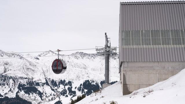 Eine Gondelbahn fährt in eine Bergstation rein