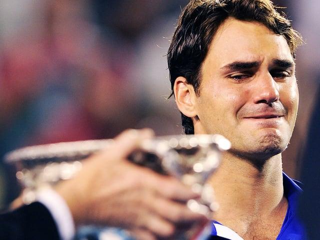 Ein Pokal wird überreicht. Federer schielt darauf und verzieht sein Gesicht.