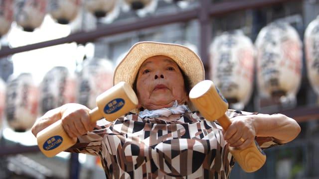 Eine Seniorin in Tokio trainiert bei einer Vorführung mit hölzernen Hanteln in ihren Händen.