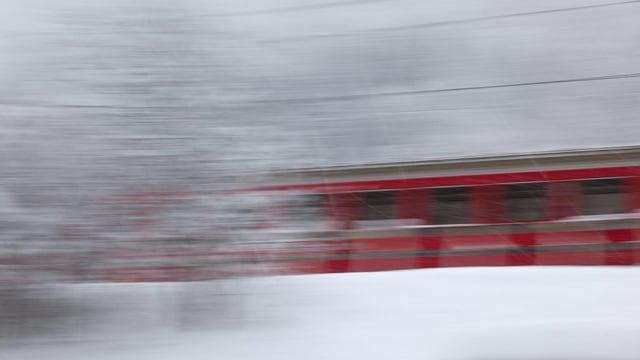 Ein Zug fährt im Schnee schnell am Fotografen vorbei