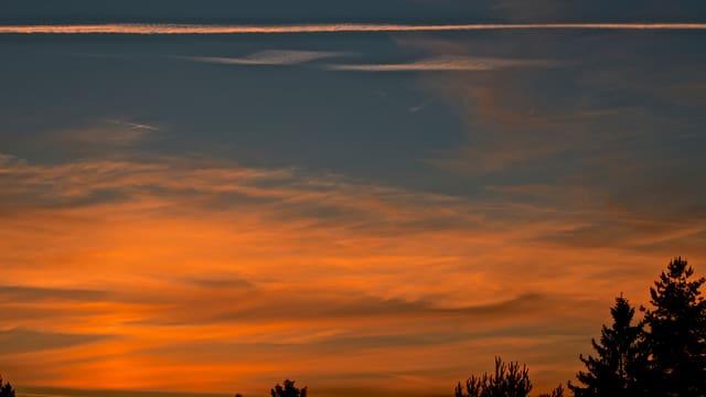 Abendstimmung mit Schleierwolken am Horizont und einer Lichtsäule an der Stelle, wo die Sonne unterging.