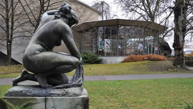 Bronzefigur vor Glaspavillon