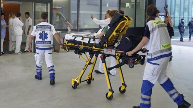 Zwei Sanitäter bringen eine verletzte Person auf einer Bare ins Kantonsspital Zug.