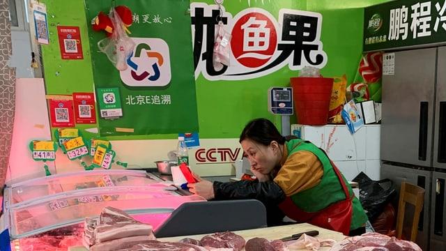 Eine Schweinefleisch-Händlerin schaut auf ihr Smartphone, während sie auf Kunden wartet.