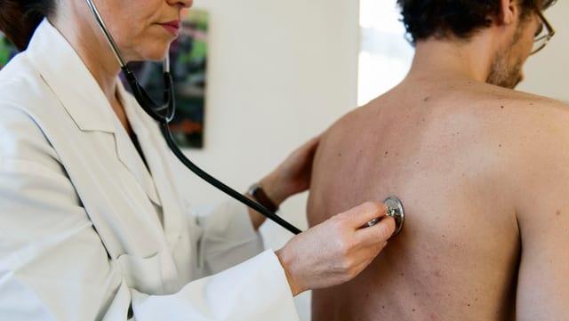 Ärztin untersucht Patienten.