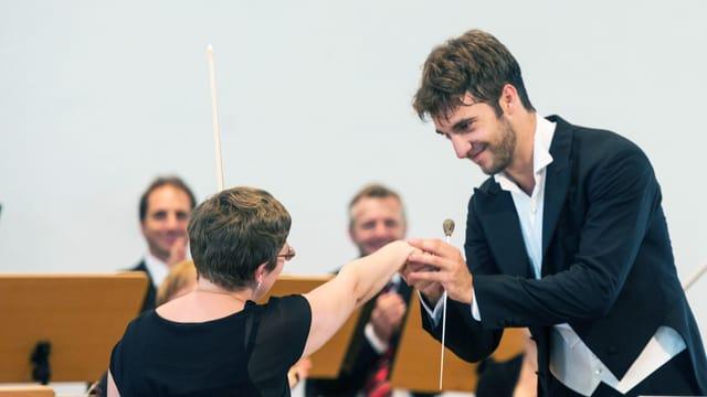 Dirigent hält die Hand einer Geigenspielerin.