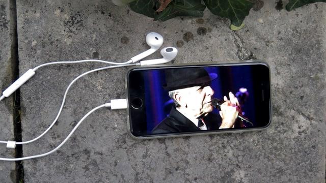 Smartphone mit Kopfhörern liegt auf einem Stein. Auf dem Display ist Leonard Cohen zu sehen.