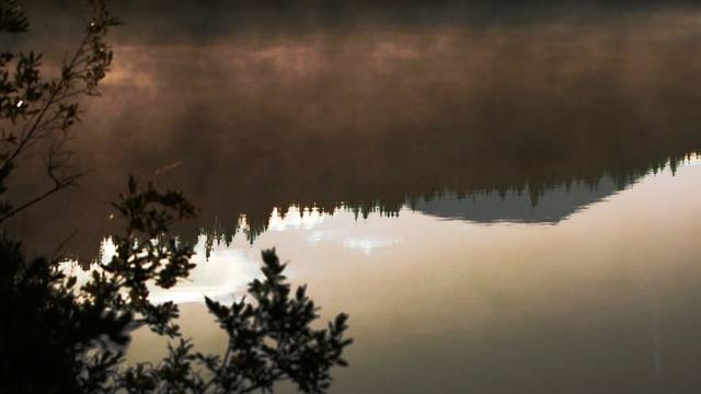 Auf einem See spiegeln sich die Berge in der Abendstimmung.
