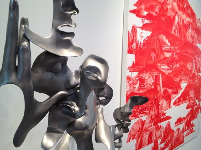 Eine Metallskulptur, dahinter rotes Gemälde.