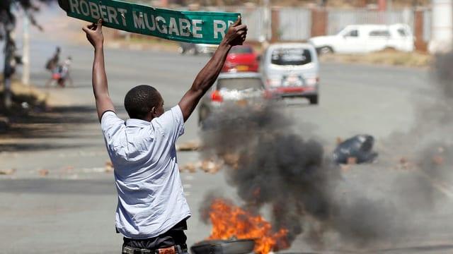 """Ein Demonstrant hält in Harare ein heruntergerissenes Strassenschild mit der Aufschrift """"Robert Mugabe Road"""" in die Höhe."""