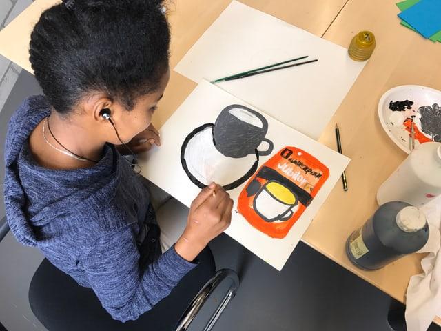 Ein Flüchtlingsmädchen sitzt am Tisch und malt eine Kaffeetasse und den dazugehörigen Bohnenbehälter.
