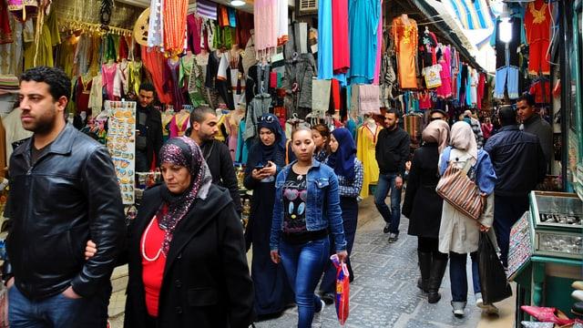 Passanten flanieren durch einen Markt in Tunis.