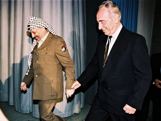 Zwei Männer gehen zusammen auf ein Podium.