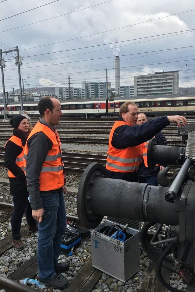 Vier Personen, einer davon montiert eine Gopro an der Vorderseite einer Lok.