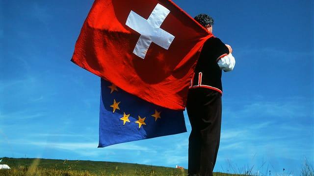 Ein Fahnenschwinger hält die Schweizer und die EU-Fahne.