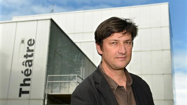 Ein Mann mit dunklem Kittel steht vor einem grauen Betongebäude mit der Aufschrift Théâtre.