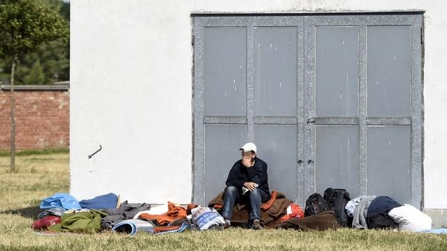 Ein Asylwerber sitzt vor einer grossen Metalltür unter freiem Himmel auf seinem Hab und Gut.