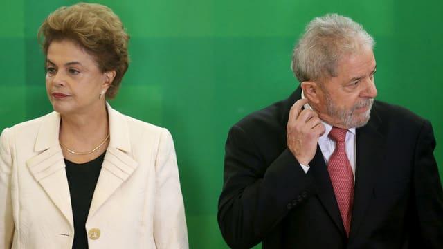 Rousseff und Lula stehen nebeneinander und blicken in unterschiedliche Richtungen, Lula kratzt sich am Ohr.
