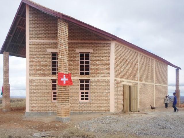 Ein braun-ranges Gebäude gebaut aus Backsteinen.