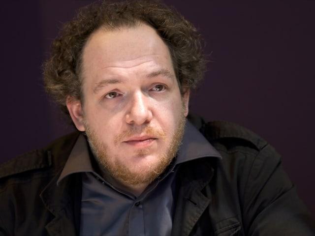 Porträtbild von Mathias Énard, er trägt ein graues dunkelgraues Hemd und ein schwazes Sacko.