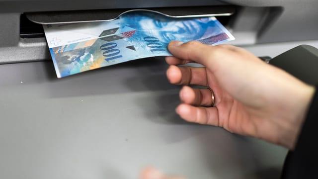 bancomat, in maun prenda la bancnota da 100 francs