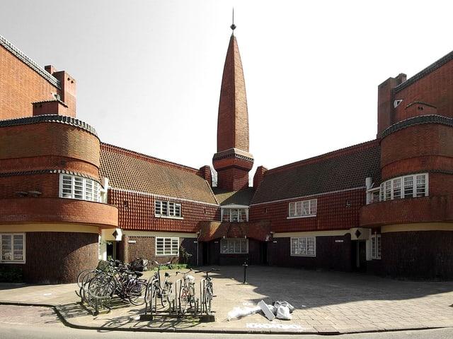 Ein Gebäude mit zwei Armen, in der Mitte raggt ein Spitz in in die Höhe.