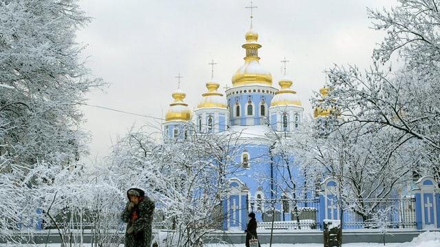 Ältere Frau stapft durch den Schnee vor einer Kathedrale mit goldenen Kuppeln.