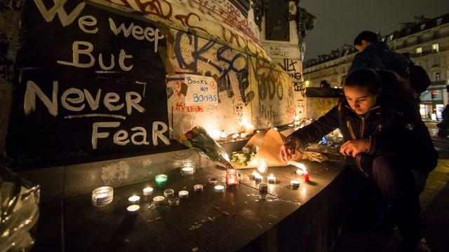 Eine Frau zündet im Gedenken an die Opfer der Anschläge von Paris eine Kerze an.