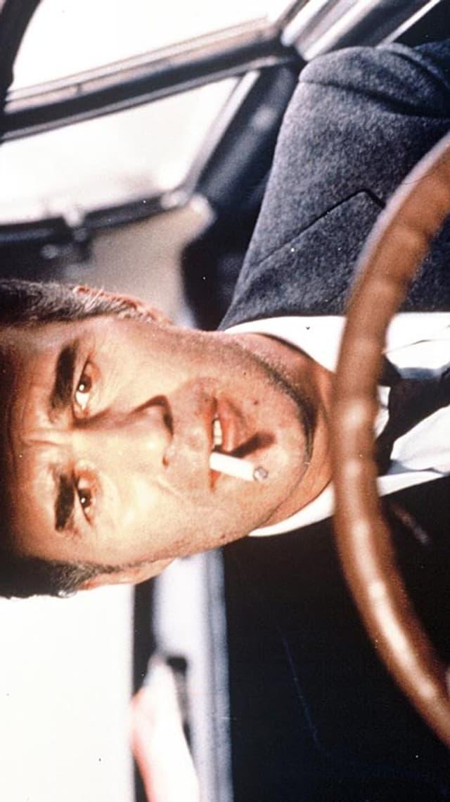 Ein Mann mit Zigarette im Mund sitz am Steuer eines Autos.