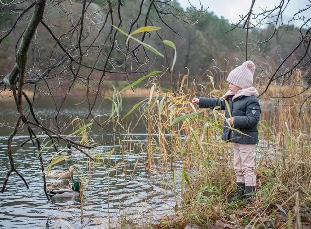 Estelle steht am Rande eines Gewässers und füttert Enten. Eingepackt in Winterkleidern