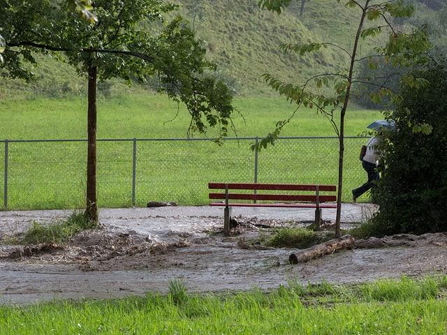 Wiese mit Weg und Bank. Alles von braunem Dreckwasser überflutet. DasWasser verwandelt den Weg in einen Strom.
