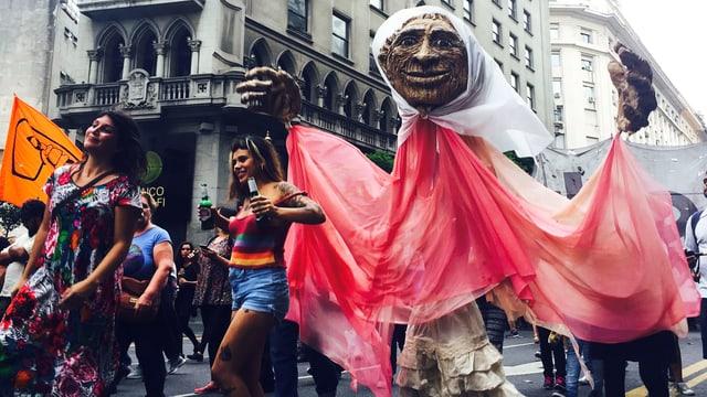 Demonstrationszug in Buenos Aires trägt eine Figur durch die Strassen.
