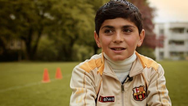 Ayham auf einer Wiese, blickt knapp an der Kamera vorbei.