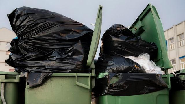 Schwarze Abfallsäcke in Containern.