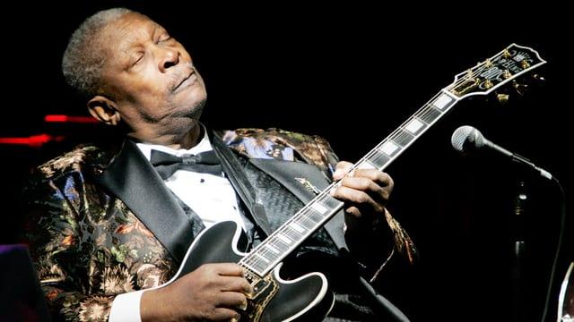 Mann mit geschlossenen Augen hält einen Gitarre in der Hand.