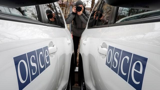 Zwei OSZE-Fahrzeuge mit Logo, Fotograf im Hintergrund