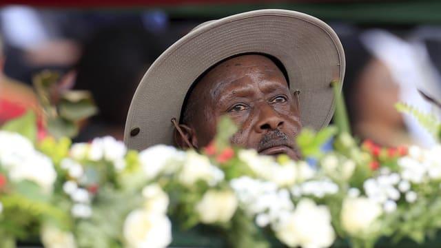 Museveni mit breitkrempligem Hut, im Vordergrund Blumen.