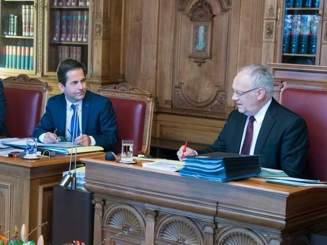 Drei Männer sitzen hinter Tischen und unterhalten sich.