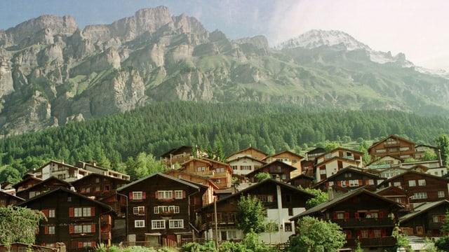 Leukerbad ann 1998 mit Holzhäusern im Vordergrund und Bergen im Hintergrund