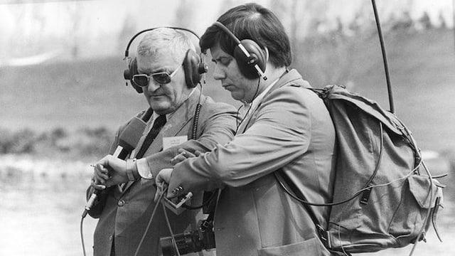 Zwei Radioreporter wartend auf die Uhr schauend