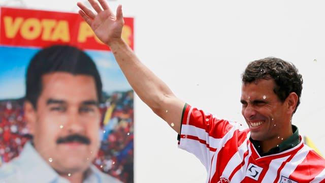Henrique Capriles winkt vor einem Plakat von Nicolas Maduro